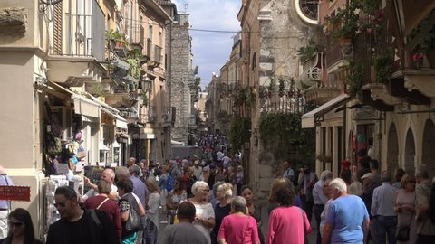 TAORMINA, SICILY/ITALY - SEPTEMBER 26, 2018: Unidentified tourists walk in main street. Taormina in metropolitan Messina has been a tourist destination since the 19th century.
