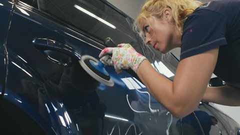 Young woman using polisher for car body polishing in auto service. Woman making car body work at car wash. Waxing car in auto service