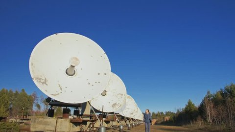 Woman student operator of institute of Solar Terrestrial Physics monitors communication equipment in notebook. Unique array solar radio telescope. Sun Solar Radio Telescope.