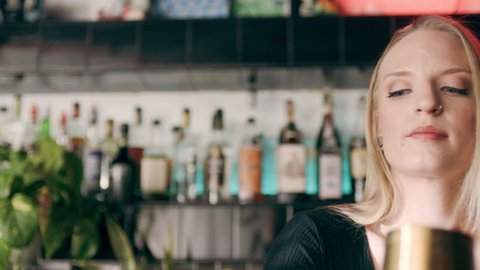 Serious and proficient barmaid, shaking a cocktail shaker in the air in a fancy bar with soft interior lighting. Close up shot on 4k RED camera.