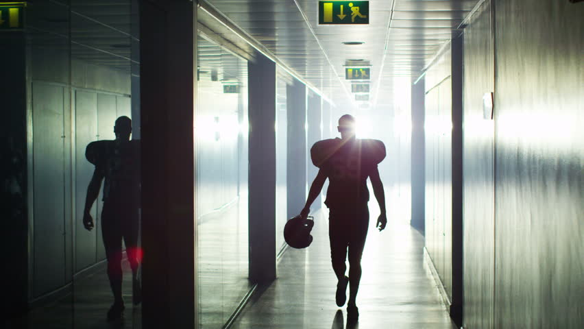 4K American football player walks alone through stadium tunnel before or after a game