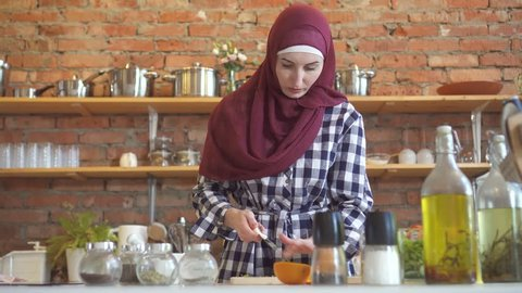Young muslim woman in kitchen cuts vegetables to cook food