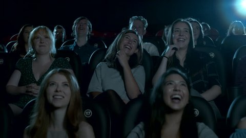 Young female movie theatre audience smiling and laughing.