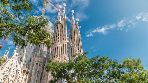 BARCELONA, SPAIN - CIRCA OCTOBER 2018: Top of Sagrada Familia, a large Roman Catholic church in Barcelona, Spain timelapse. Spires and cranes. Green trees, blue cloudy sky at autumn day