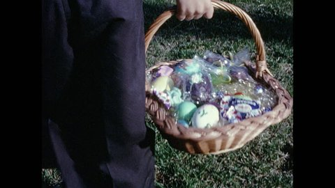 1970s: Boys carry Easter baskets over to woman sitting on wall, sit down next to woman and look at eggs in baskets.