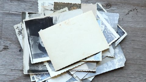 Man puts old photos on a wooden table. Old faded dirty photos and blank empty templates. mock-up