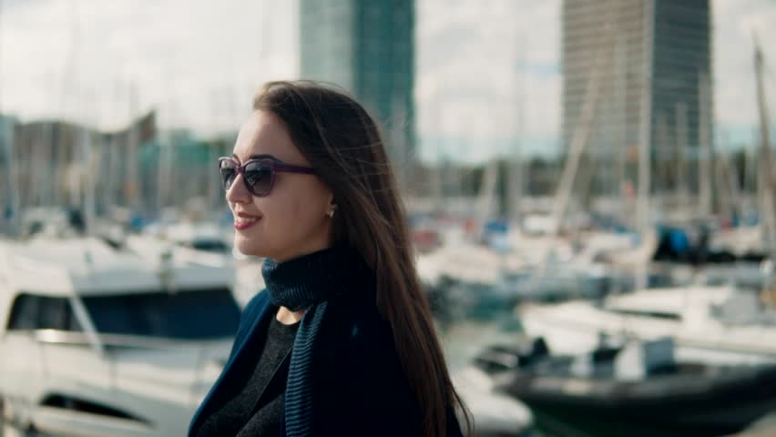 Woman in sunglasses walking with a lot of yachts and boats behind. Slow motion | Shutterstock HD Video #1019656372