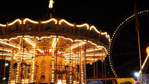 Fascinating flashing lights dark night sky illumination of vintage merry go round fair carousel ferris wheel at carnival