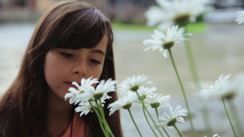 Pretty Caucasian brown-haired girl in casual clothes sitting near white flowers and smelling camomiles. Close-up. Beauty of nature. Outside.