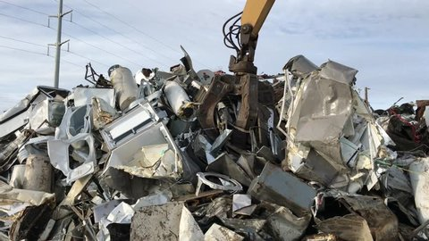 Claw machine dropping metal after clasping over mound of various metallic scrap in salvage yard.