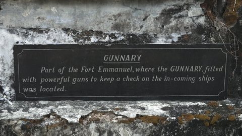 Close up steady shot of sign post, fort Emmanuel ruins where gunnery  was stationed. Disfigured block walls, protected the hidden powerful guns from counter-attacks from incoming ships, India's touris