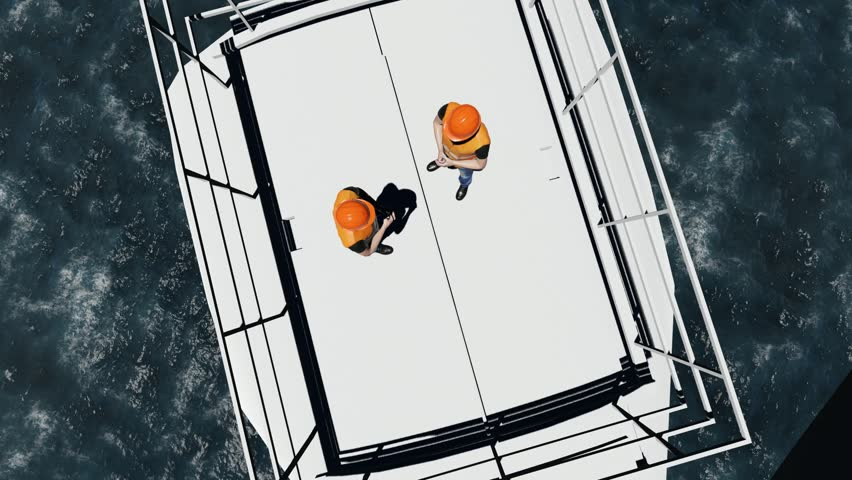 Two offshore workers on the top of the windmill, wind farm
