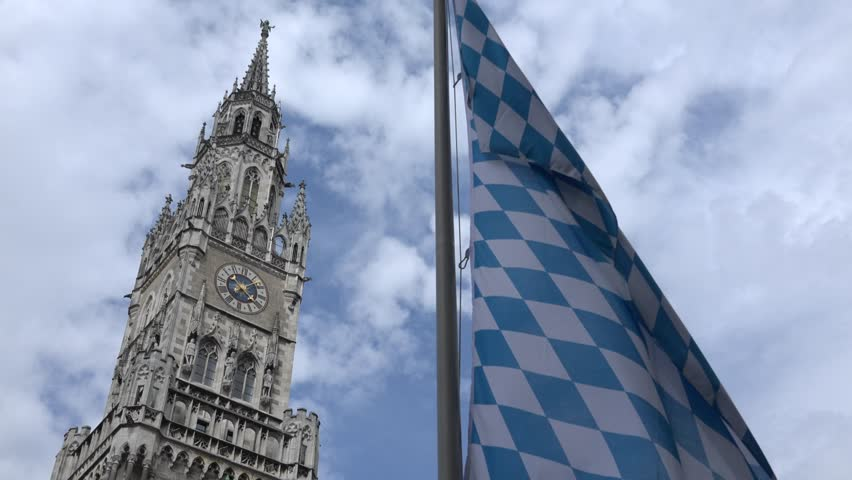 ULTRA HD 4K New town hall tower with public clock in Munich with local flag, landmark in sunny day