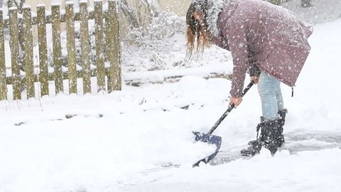Slow motion of young woman, female in winter coat cleaning, shoveling driveway, street, road from snow in heavy snowing snowstorm with shovel, residential houses, wooden fence, trees, bushes