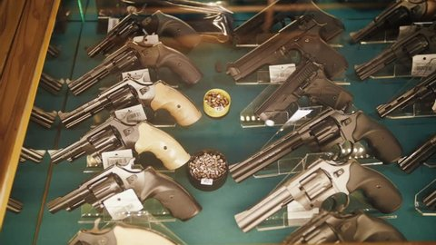 Different guns and revolvers on shelves store weapons on shop center.