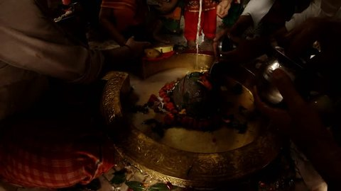 Rishikesh, Uttarakhand / India - July 30, 2018: hands do puja ritual prayer with candle to swayambhu natural lingam another people put on shivlinga flowers leaves of bilva and prasad pour water