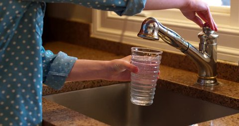 Young Woman fills Water Glass with Tap Water at Nice Sink with Granite Counter Top