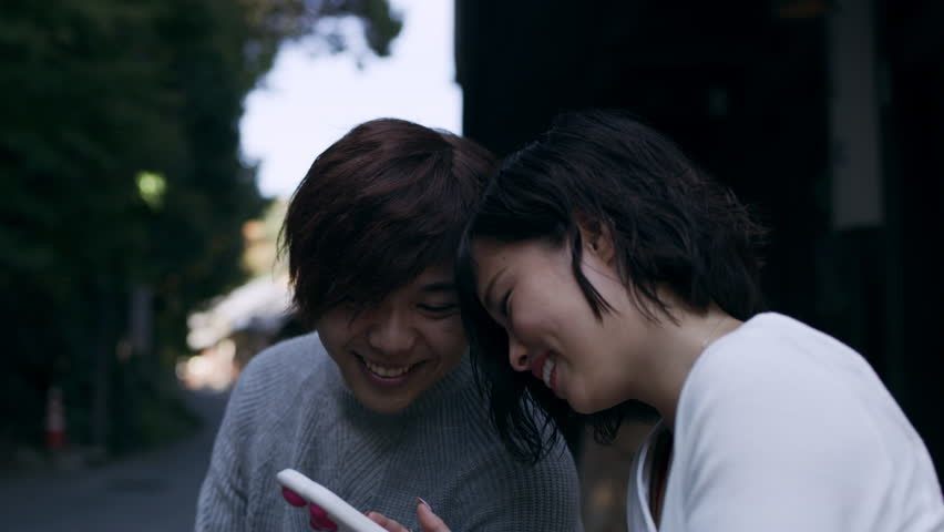 Young couple sitting outside and looking on the girlfriend's phone happily in Kyoto, Japan with soft natural lighting. Close up to wide shot on 4k RED camera on a gimbal. | Shutterstock HD Video #1019850772