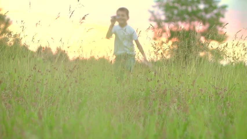 Happy Boy playing with paper airplane on the field over sunset background. Kid throws a paper plane, dream, freedom concept. Slow motion video footage 240 fps. Full HD 1080p. High speed camera