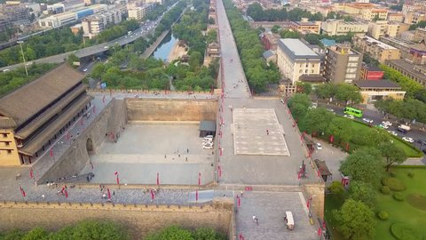 Sunset aerial view of tourists & local people riding bike on Xian Ancient City Wall. Xian, China