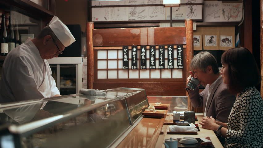 Cheerful Japanese couple appreciating the sushi that the Master chef is preparing in small sushi bar with soft interior lighting. Close up shot on 4k RED camera. | Shutterstock HD Video #1019910562