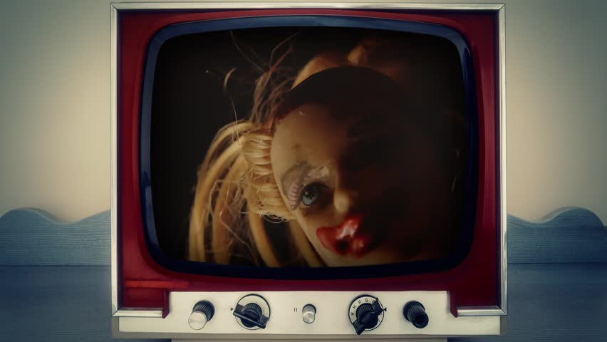 A retro vintage TV showing a scary cursed doll appearing, with red blood on her lips and hair. Close-up shot.  | Shutterstock HD Video #1019933962