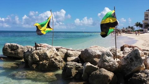 Aerial footage of jamaican flags on a beautiful tropical caribbean beach on Jamaica