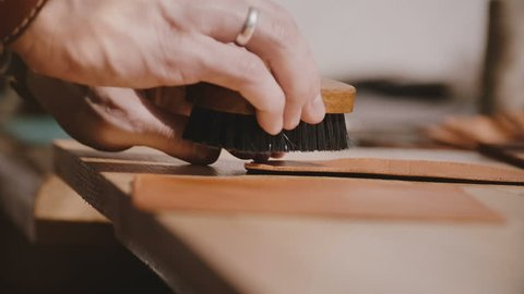 Close-up shot of professional male artisan hands polishing leather for handmade goods with special abrasive finish brush