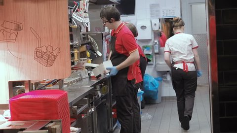 Moscow, Russia - September 16, 2018: Men and Women Works in the Kitchen Fast Food Restaurant Chain. McDonald's Kitchen Staff in the working process. Workflow Kitchen Fast Food Cafe