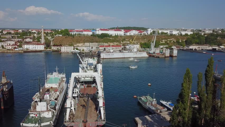 SEVASTOPOL, RUSSIA - JUN 10, 2018: Many ships and boats are in city port at summer sunny day. Aerial view   Shutterstock HD Video #1020099202
