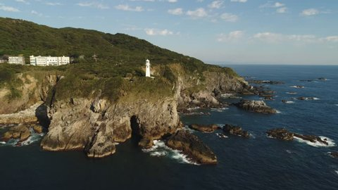 Aerial pull back on the coast of Japan with lighthouse in the background