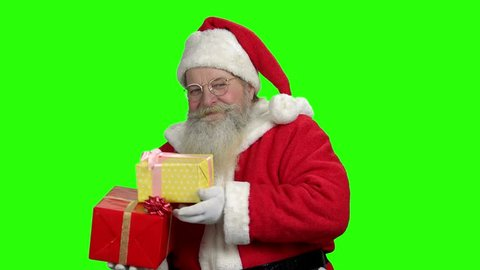4f9ecf4b8d72b Old smiling Santa showing thumb up. Cheerful Santa Claus holding gift boxes  on green screen