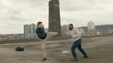 Two men fight on a warehouse rooftop with skilled kicks and punches in overcast sunlight. Medium shot in 4K with an Alexa Mini camera