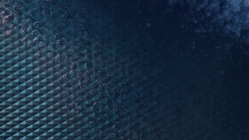 This is a creative artistic macro video of colorful blue abstract shapes on a metal background in water allowing for a lot of copy space for worship lyrics