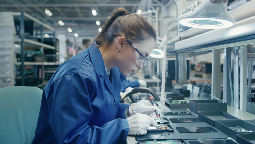 Woman Electronics Factory Worker in Blue Work Coat and Protective Glasses is Assembling Smartphones with Tweezers and Screwdriver. High Tech Factory Facility with more Employees in the Background.  | Shutterstock HD Video #1020186892
