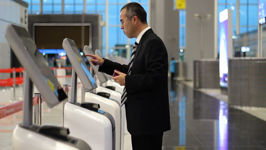 Passenger business man at the airport check in ticket at kiosk terminal