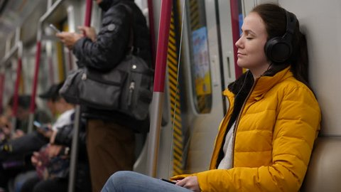 Young adult woman sit with eyes closed in metro train, listen music, large earphones on head. Blurred background, subway car ride between stations. Tired but satisfied person rest at public transport