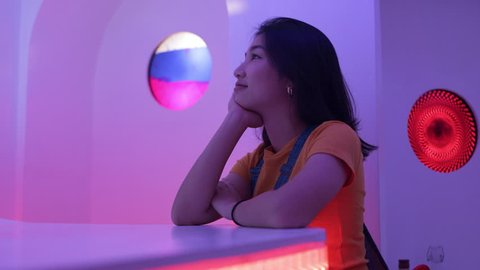 Pensive Japanese woman sitting at a bar  with soft interior funky colorful lighting. Medium shot on 4k RED camera on a gimbal.