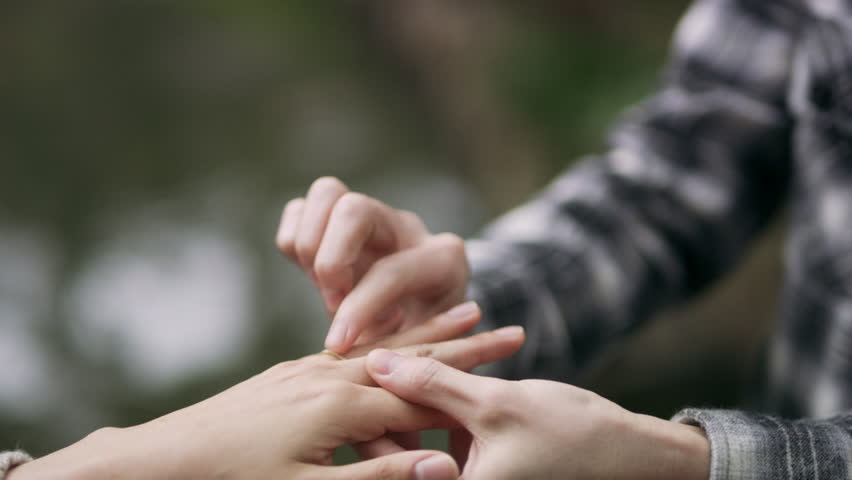 Overjoyed Japanese man presenting a ring to his girlfriend, places it on her finger and hugs her happily in a beautiful garden with soft natural lighting. Close up shot on 4k RED camera.