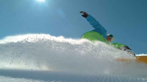 SLOW MOTION TIME REMAP, CLOSE UP Extreme snowboarder carving downhill, spraying snow into camera. Smiling active man snowboarding on groomed ski slope in mountain resort. Cheerful snowboarder turning