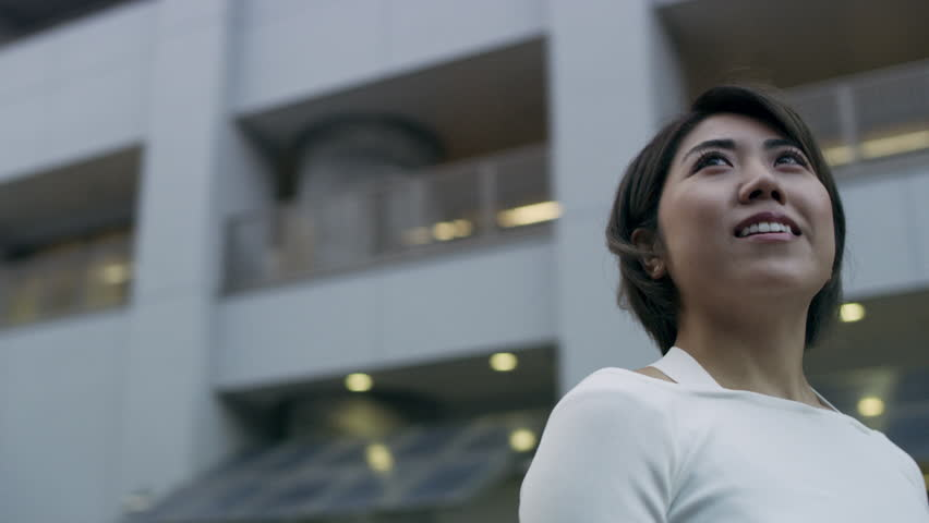Smiling Japanese woman looking out while standing in a quiet metropolitan city in Japan with soft natural lighting. Medium close up shot on 4k RED camera on gimbal.