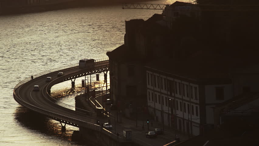 Automobiles on route above river near old buildings at sunset in Porto, Portugal | Shutterstock HD Video #1020295582