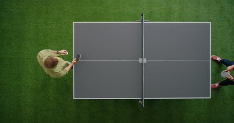two young men playing ping pong game enjoying competitive sport in modern recreational workspace top view