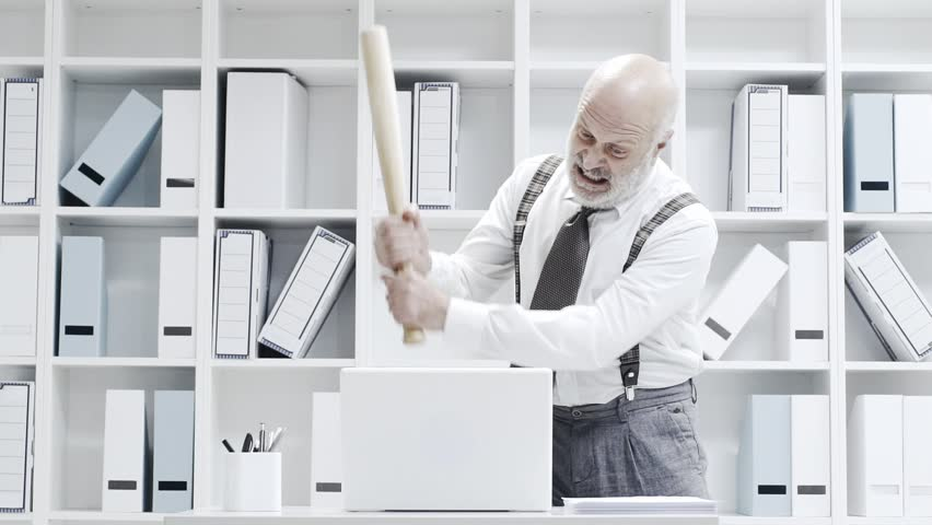 Stressed crazy businessman smashing his laptop in the office using a baseball bat, anger and computer problem concept | Shutterstock HD Video #1020353692