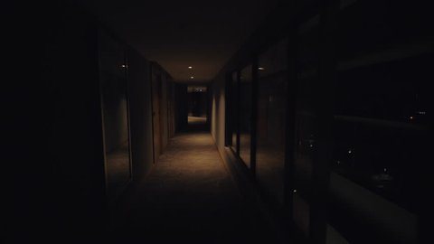 A steadicam shot of a long dark hotel hallway. The wooden doors on one side of the corridor and large shiny windows on another. The warm yellow light is muted that gives the interior some mysterious