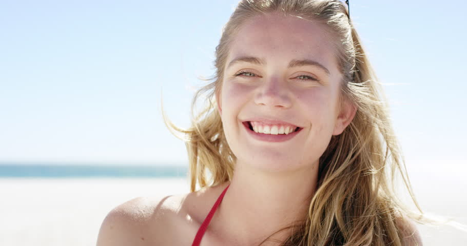 Close up portrait of beautiful young teenage girl smiling on tropical beach slow motion