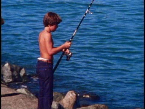 SAUSALITO, CALIFORNIA, 1979, Young boy, shirtless, with rod and reel fishing