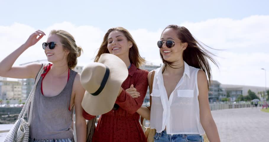 Three young women tourists on summer vacation girl friends walking on beach promenade wearing denim shorts