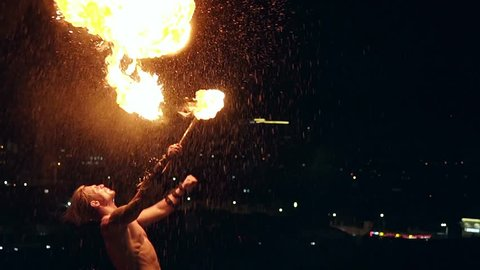 Young blond male artist breathes out large stream of fire multiple times making show. Slow motion shot.