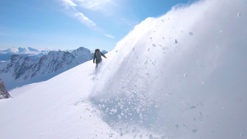 Young female snowboarder heliskiing in stunning British Columbia during her active winter holiday. Unrecognizable woman heliboarding remote pristine slopes in the picturesque Canadian mountains.